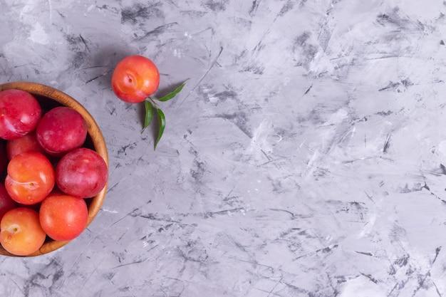 Dojrzałe czerwone śliwki w drewnianym talerzu
