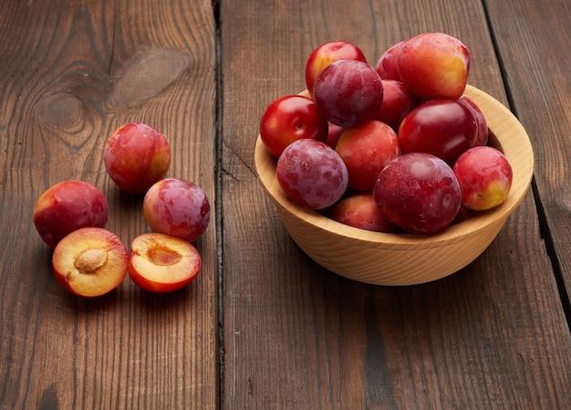 Dojrzałe czerwone śliwki w okrągłym drewnianym talerzu na stole