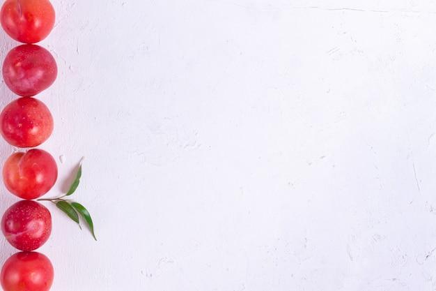 Dojrzałe czerwone śliwki z zielonymi liśćmi z drzewa