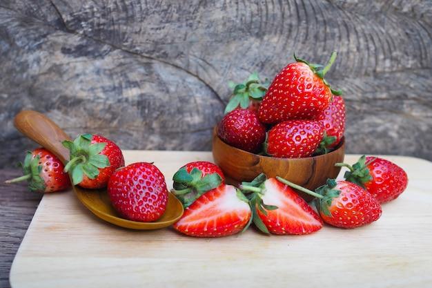 Dojrzałe czerwone truskawki w drewnianym pucharze na drewnianym stołowym tle