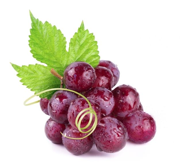Dojrzałe czerwone winogrona w kroplach wody na białym tle