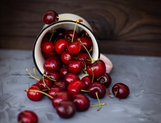 Dojrzałe czerwone wiśnie w okręgu na szarym stole z bliska