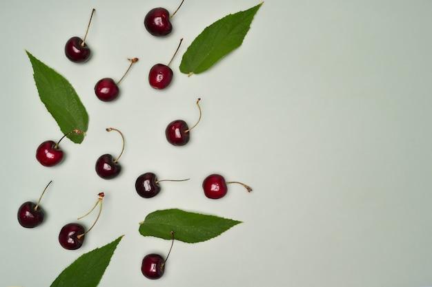 Dojrzałe czerwone wiśnie z liśćmi na zielonym tle.