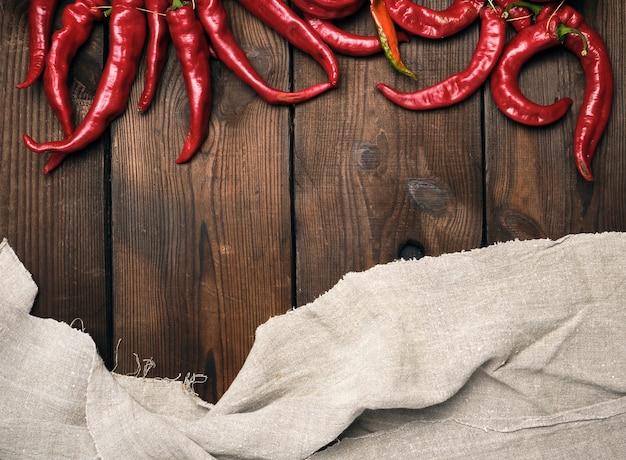 Dojrzałe czerwonego chili pieprze na brown drewnianym rocznika tle od desek