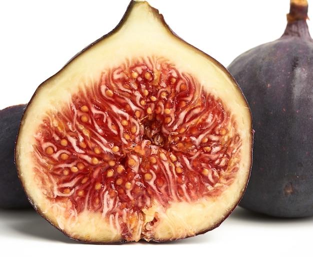 Dojrzałe figi fioletowe całe i przepołowione na białym tle
