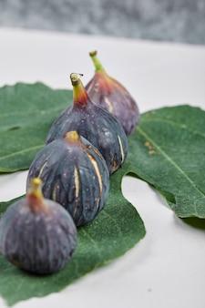 Dojrzałe figi fioletowe z liściem na białym tle.