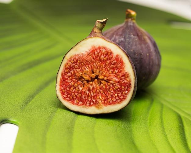 Dojrzałe fioletowe soczyste figi na zielonym liściu