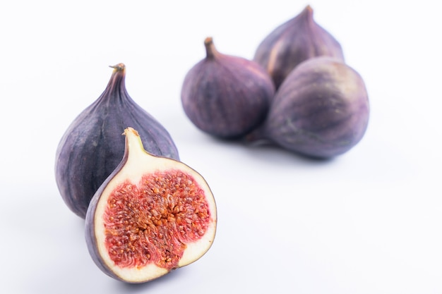 Dojrzałe fioletowe surowe figi na białym tle na białym tle, całe i przecięte na pół