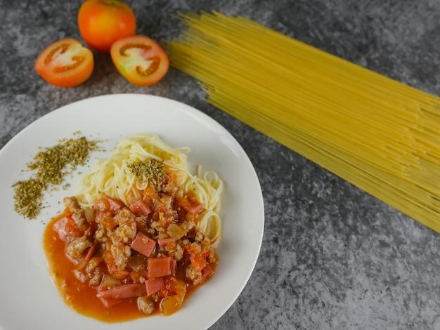 Dojrzałe gotowane makaron spaghetti pomidorowy oregano w białej płytce