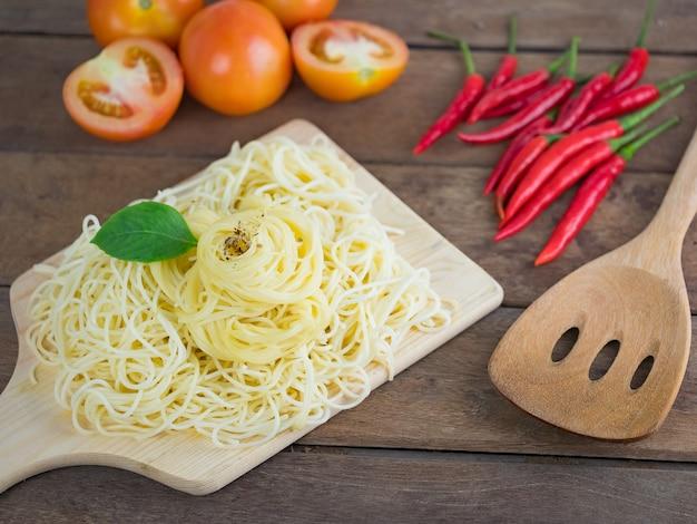 Dojrzałe gotowane spaghetti makaron na drewnianej desce do krojenia