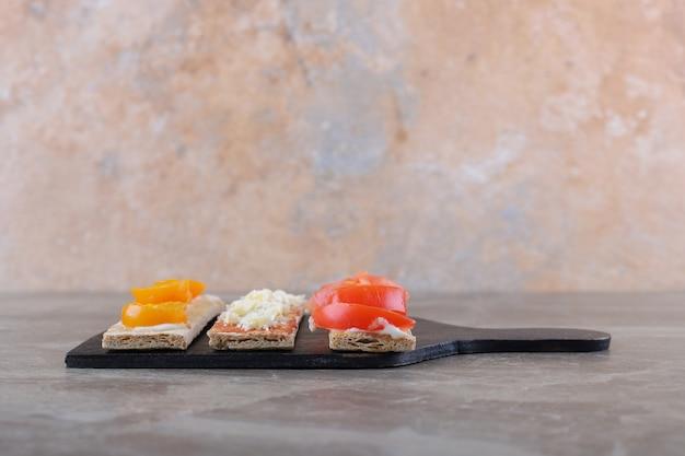 Dojrzałe i niedojrzałe pomidory pokrojone w plastry na chrupiącym pieczywie na desce do krojenia, na marmurowej powierzchni
