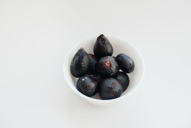 Dojrzałe i słodkie figi pokrojone i ułożone w talerz na białym tle z wolną przestrzenią. owoce i wegetarianizm.