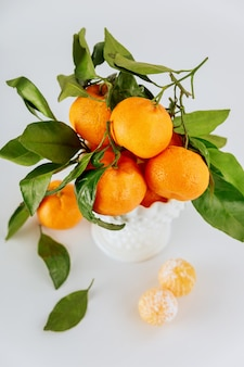 Dojrzałe i soczyste mandarynki z zielonymi liśćmi.