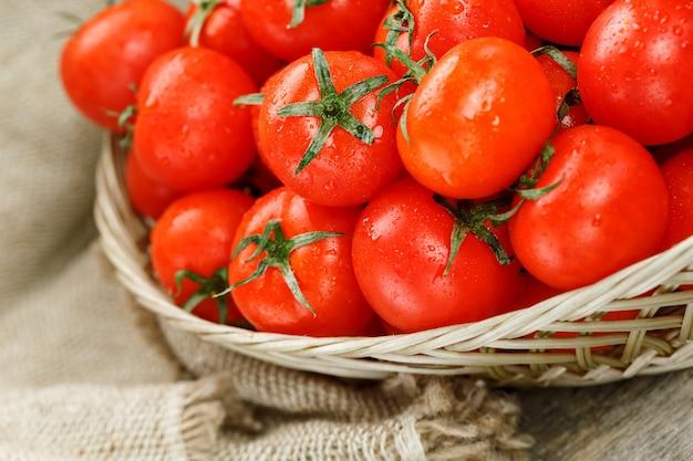 Dojrzałe i soczyste pomidory koktajlowe z kroplami wilgoci w wiklinowym koszu. stary drewniany stół, wokół płótna z płótna