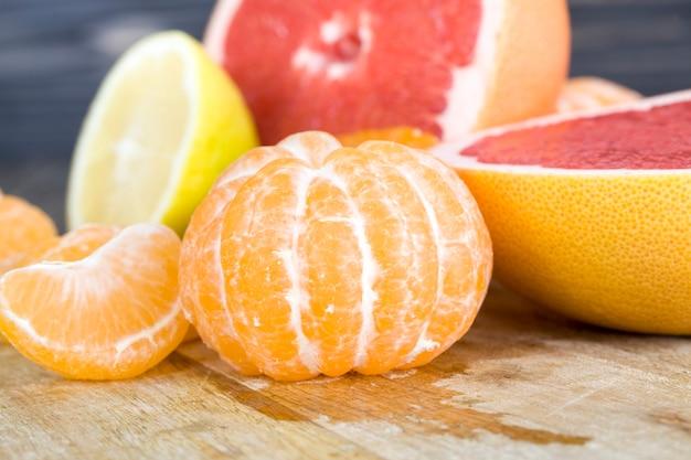 Dojrzałe i soczyste różne owoce cytrusowe razem w dużym stosie, mandarynki, grejpfruty