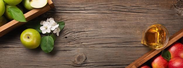 Dojrzałe jabłka czerwone i zielone w drewnianym pudełku z gałęzi białych kwiatów i szklanką świeżego soku na drewnianym stole. panoramiczny widok z góry.