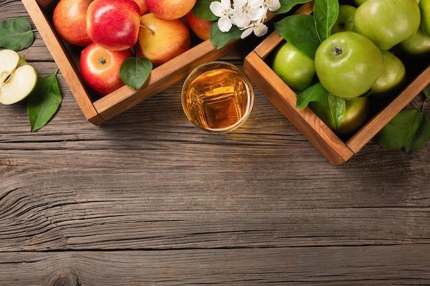 Dojrzałe jabłka czerwone i zielone w drewnianym pudełku z gałęzi białych kwiatów i szklanką świeżego soku na drewnianym stole. widok z góry z miejscem na tekst.