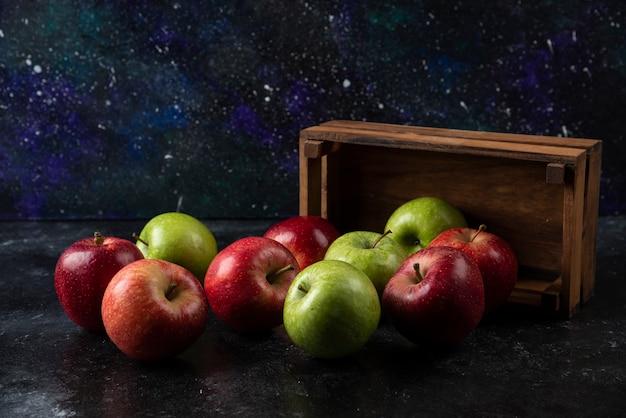 Dojrzałe jabłka ekologiczne z drewnianego pudełka na czarnej powierzchni. .
