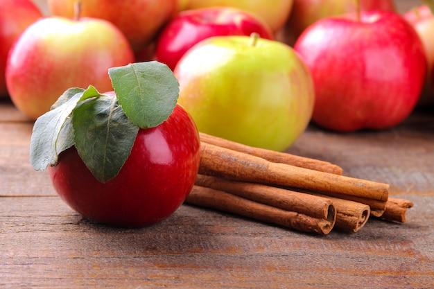 Dojrzałe jabłka i laski cynamonu na tle drewnianych