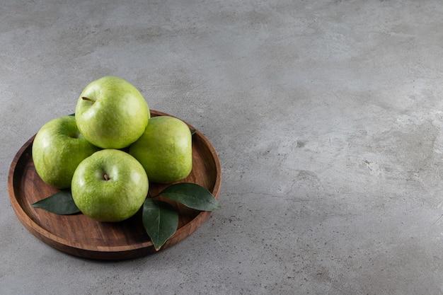 Dojrzałe jabłka na drewnianym talerzu, na marmurowym stole.