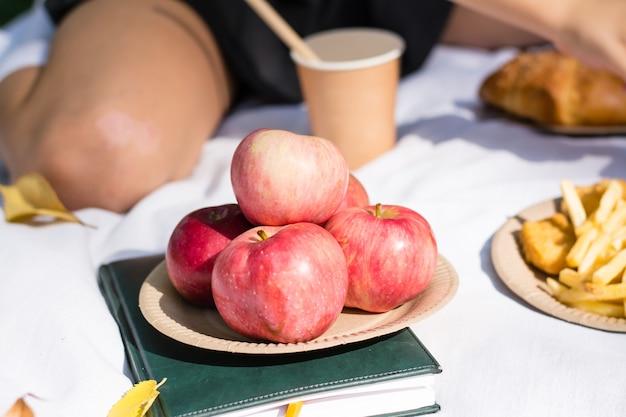 Dojrzałe jabłka na eko talerzu na pikniku dla uczniów w słonecznym jesiennym parku. ekologiczna jednorazowa zastawa stołowa. szkolne posiłki