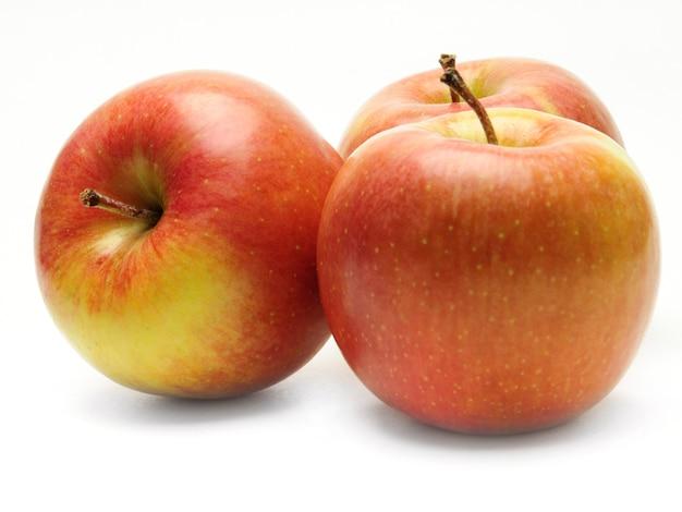 Dojrzałe jabłka na odosobnionej białej powierzchni