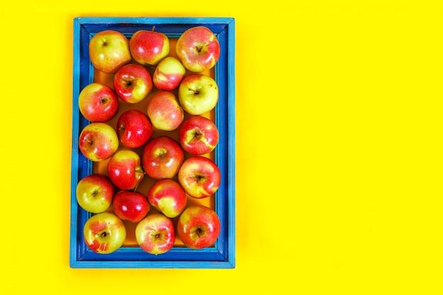Dojrzałe jabłka na żółtym tle