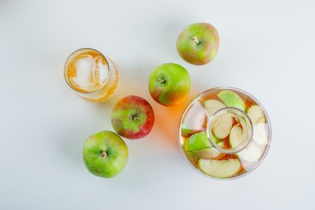 Dojrzałe jabłka z sokiem na białym tle