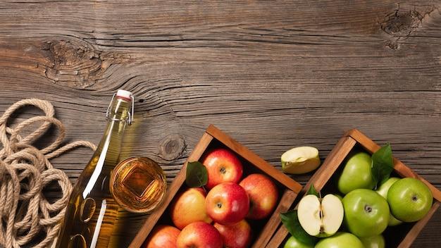 Dojrzałe jabłka zielone i czerwone w drewnianym pudełku z gałęzi białych kwiatów, szkła i butelki cydru na drewnianym stole. widok z góry z miejscem na tekst.