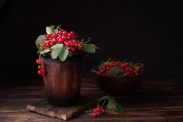 Dojrzałe jagody czerwonej porzeczki w glinianej misce na ciemnym tle, letnie jagody, z bliska.