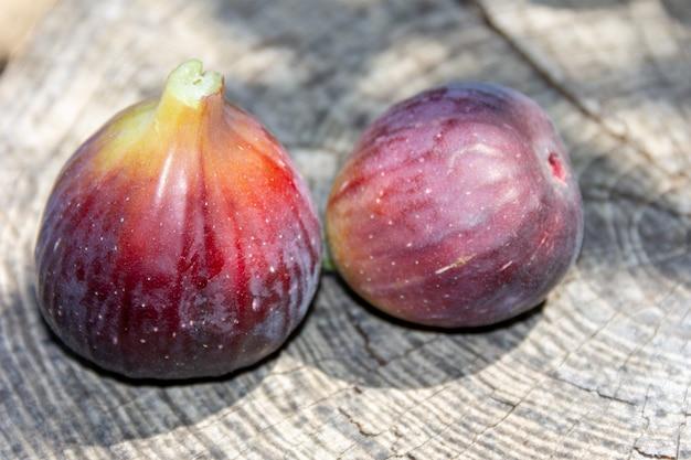 Dojrzałe jagody figowe na szarym drewnianym tle z bliska