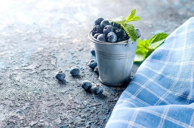 Dojrzałe jagody jagody w mini wiaderku z liśćmi mięty na ciemnym tle