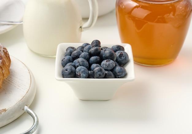 Dojrzałe jagody w białym ceramicznym talerzu na białym stole, składniki śniadaniowe