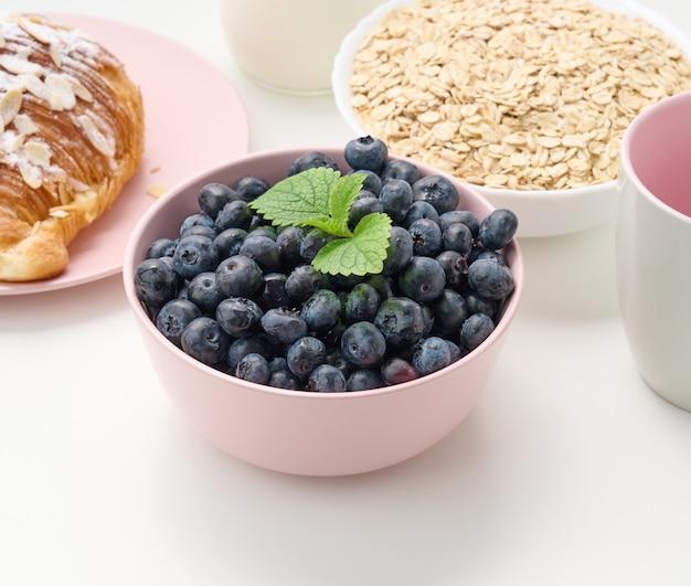 Dojrzałe jagody w różowym ceramicznym talerzu na białym stole, składniki śniadaniowe