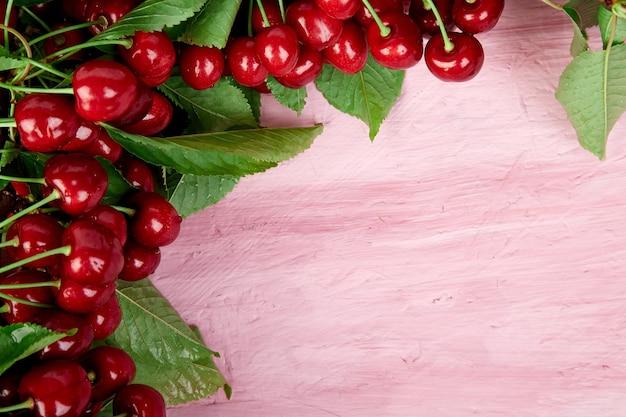 Dojrzałe jagody wiśni i liść wiśni na różowym tle