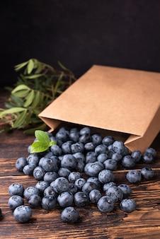 Dojrzałe jagody wysypujące się z papierowej torby na zakupy na ciemnym tle drewnianych, letnie jagody.