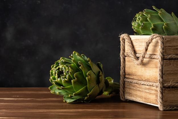 Dojrzałe karczochy organiczne na rustykalnym drewnianym stole.