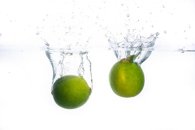 Dojrzałe limonki wpadają do wody. rozpryskuje się woda
