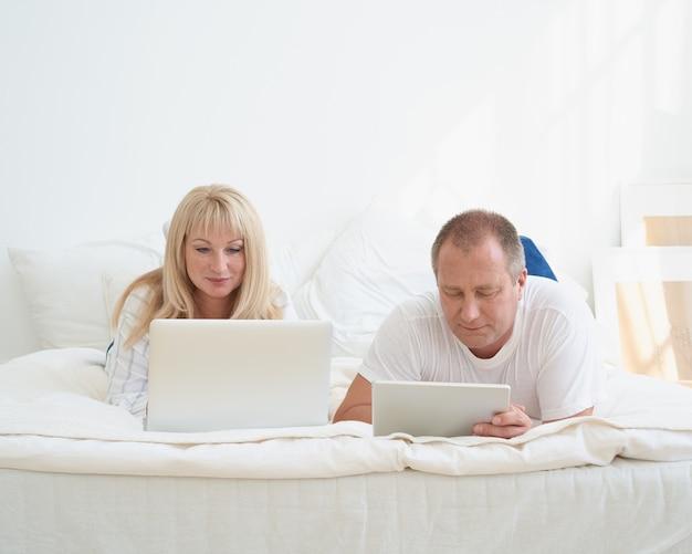 Dojrzałe małżeństwo planuje podróż, wybiera wakacje, szuka biletów, rezerwuje hotel.