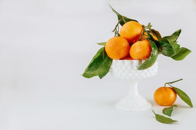 Dojrzałe mandarynki florida z zielonymi liśćmi w białej misce.