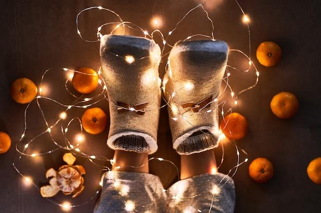 Dojrzałe mandarynki pomarańczowe, ciepła biała girlanda bożonarodzeniowa i kobiece nogi w ciepłych puszystych miękkich zimowych kapciach w przytulnym domu w wigilię bożego narodzenia. widok z góry