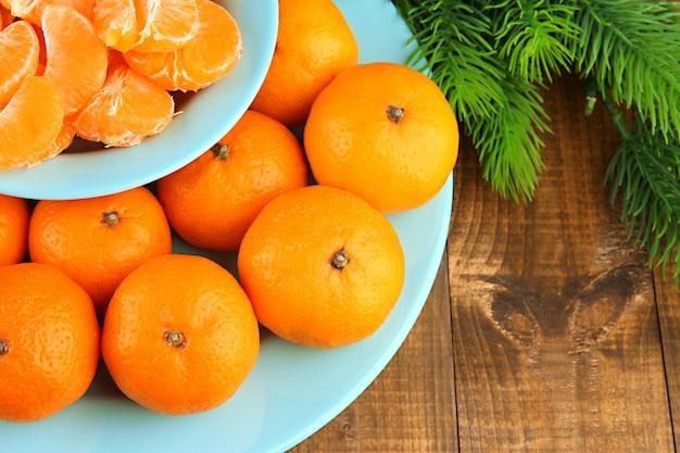 Dojrzałe mandarynki w misce z gałązką jodły z bliska