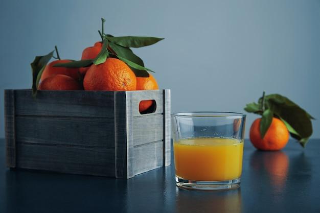 Dojrzałe mandarynki w starym pudełku z liśćmi na rustykalnym niebieskim stole