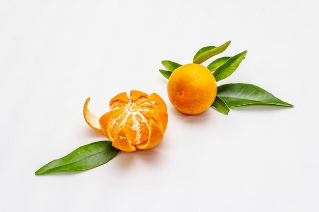 Dojrzałe mandarynki z liśćmi. świeże owoce na białym tle