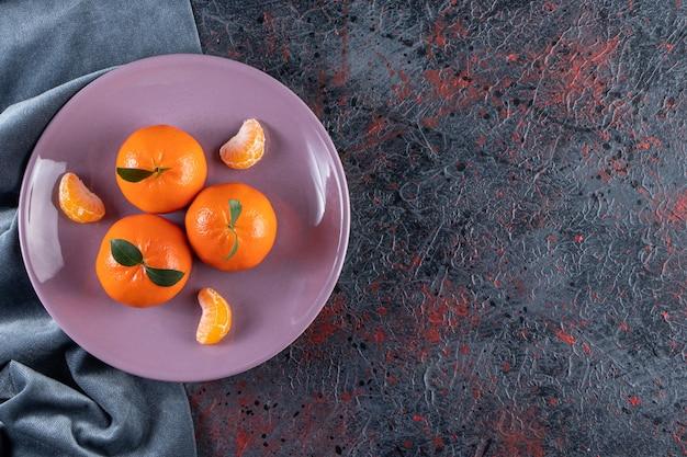 Dojrzałe mandarynki z liśćmi ułożonymi na fioletowym talerzu.