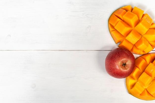 Dojrzałe mango i jabłka na białym drewnianym stole