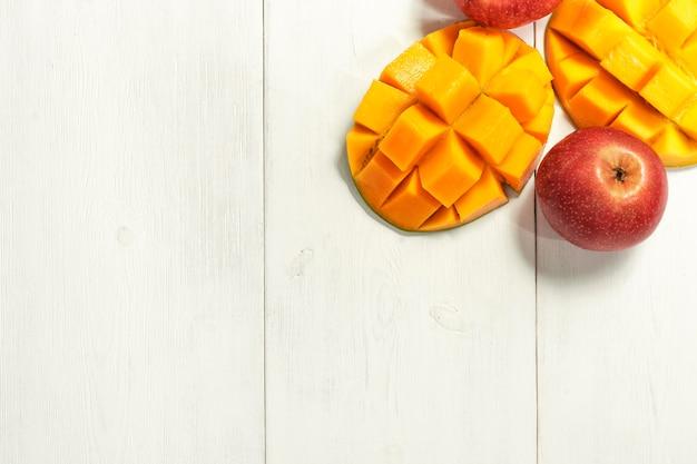 Dojrzałe mango i jabłka na białym drewnianym widoku z góry