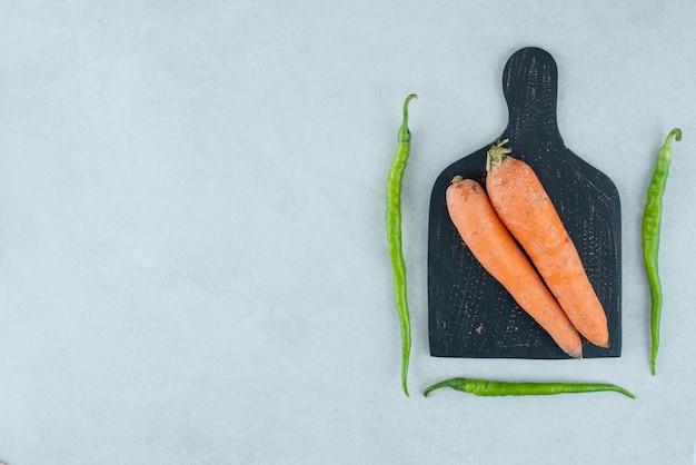 Dojrzałe marchewki i papryki na ciemnej desce.