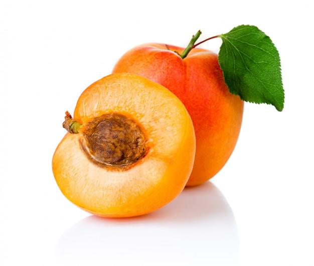 Dojrzałe morelowe owoc zz zielonym liściem i plasterkiem odizolowywającymi