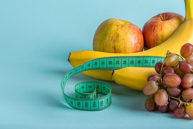 Dojrzałe owoc i pomiarowa taśma na błękitnej przestrzeni. pojęcie diety i właściwego odżywiania.